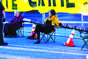 Observer file photo by Al Frey Activists Doug Smith (left) and Ulrike von Motke sit chained to a replica pipeline in Williston in September.  The six arrested, all grandparents, said they were supported by a group of young protesters who stood with them.