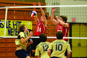 CVU's Jeff Boliba (24) and Spencer Snipes get the block during the first VPA santioned boys volleyball championship at St.Michael's College on Saturday.