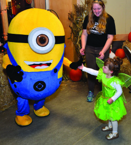 Stella Haas (2-1/2) carefully slaps 5 with a Minion at the Halloween Express pre-ride party at Burlington's Echo Center on Sunday the 30th.