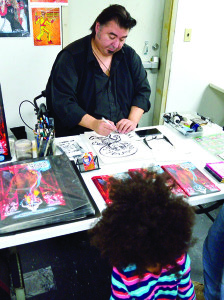 Local comic book artist and creator Greg Giordano compltetes a caricature of Anaia Daoust (3) at the opening of Killer Rabbit Comics and Games at the Taft Corners shopping center on Saturday the 19th.