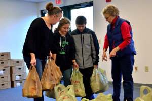 Mom, Laura, and twins Ava and Jacob Medici donate turkeys and other food items at the Williston Community Food Shelf on Saturday's Turkey Day Giveaway. Volunteer, Ginger Morton, is there to receive the donation for WCFS.