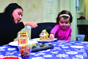 Observer photo by Al Frey Paulina Thompson helps daughter, Alessandra, 2, with her gingerbread house during the Dorothy Alling Library holiday party on Saturday, Dec.3.