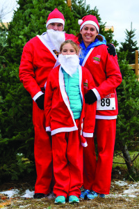 Santa Claus and family, AKA (L to R) Chris, Piper (8) and Lisa Thompson search for the perfect tree at Isham's Family Farm in Williston on December 4th to take back to the North Pole.