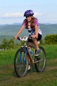 Gretchen Kogut rides with the Green Mountains in the background during the Wednesday night races at Catamount.