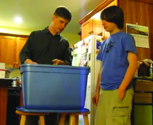 Observer courtesy photo Writer Luc Reid and his son add worms to their indoor vermiculture compost bin in a video.