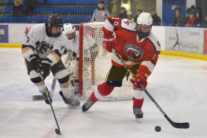 Jennings Lobel plays the puck behind the Essex net during CVU's hockey game versus Essex at the Essex skating facility on Saturday the 28th.