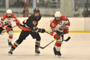 Joey Parento tips the puck ahead of Middlebury's Jake Peluso during CVU's quarterfinal game with Middlebury on March 4th at Cairns Arena.