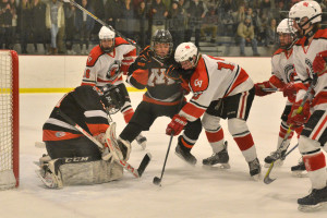 Jennings Lobel battes in front of Middlebury's goalie, Doug DeLorenzo  during CVU's quarterfinal game with Middlebury on March 4th at Cairns Arena.