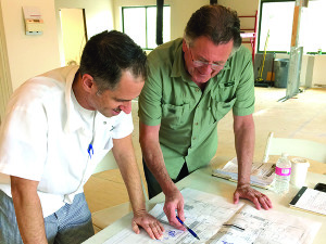 Observer photo by Marianne Apfelbam Chef's Corner co-owners Scott Sorrell and Jozef Harrewyn look over the blueprints for their new space on Cornerstone Drive.
