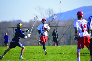 Long stick defender, Tyler Parker Pawloski, clears the ball forward at CVU's lacrosse game with Essex on Tuesday the18th in Hinesburg.