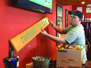 Observer photo by Jason Starr Owner Stewart Corey removes a sign from behind the bar at Mexicali Grill and Cantina in Maple Tree Place on Wednesday. The 22-year-old Williston restaurant was evicted from the property last week.