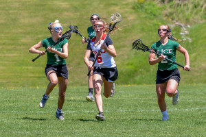 Gabby Booth streaks ahead of two defenders during their game versus Rice High School on Saturday May 20th in Hinesburg.