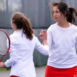 Megan Watson (L) celebrates a point with her doubles partner Matty Huber during CVU's MAtch with South Burlington on Wednesday, May 3rd in So Burlington.