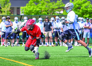 Jake Evans scoops up a ground ball during the boys D1 lacrosse championship at UVM's Virtue Field versus South Burlington on Saturday the 10th.