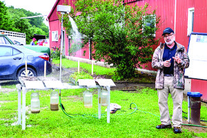 """Danny Peet from the Williston office of the National Resources Conservation Service (NRCS) explains how the """"rainfall simulator""""  shows how much absorbtion and run-off rates vary with soil conditions."""