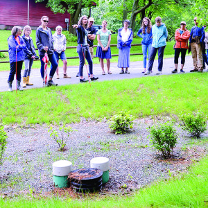 Becky Tharp points out the rain garden which is part of Lefebvre Lane's gentle stormwater management solution during the Williston Sustainability Solutions Tour on Saturday.