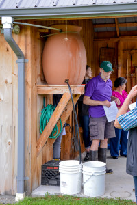Chapin Kaynor (green cap) explains his rainwater collection and run-off  control system during the Williston Sustainability Solutions Tour on Saturday the 8th.