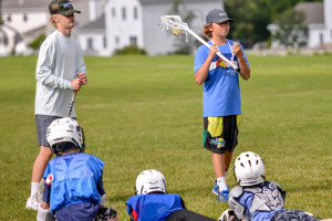 WCS 8th Grader, Will Bartley, whistle in hand, is giving instruction in lacrosse to a group of 4th and 5th grade boys for his 8th Grade Challenge Project.