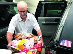 Observer photo by Jason Starr Williston Community Food Shelf volunteer Gary Frymire helps a client pack a car with groceries Tuesday.