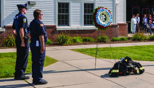 Police Officer Dan Macaig and Fire Fighter George Shortsleeves lay a memorial wreath at the base of the flag pole during the 9-11 remembrance service in Williston on Monday.