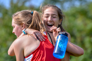 Willow DeVoe-Talluto (R) hugs Lila Carleton to celebrate their first place finish in the girls JV race at the CVU Relays on Saturday.