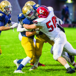 Jake Bortnick (50) makes the tackle during CVU's game vs Essex at Essex High on Friday evening.