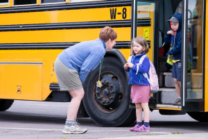 Kindergarten TA, Celeste Plouffe, provides some needed assistance to one of the new students on the first day of Kindergarten at Allen Brook School on Thursday.