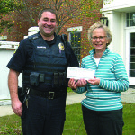 Observer photo by Jason Starr Williston Community Food Shelf President Ginger Morton accepts a $5,192 check for the nonprofit last week from Officer Travis Trybulski, president of the Williston Police Officers' Association. The money was raised at the Williston Chowder Challenge event Oct. 1.