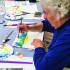 Williston artitst, Nancy Stone works on her painting for the Williston Community Peace Project at Williston's library on Wednesday evening