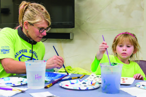 Poppy Crowther (5) paints with her Mom, Cara for the Williston Community Peace Project at Williston's library on Wednesday evening.