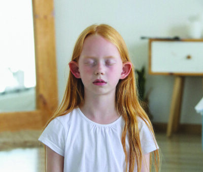 Young girl sits meditatively with eyes closed.
