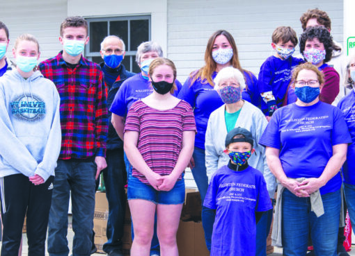 Masked food drive volunteers at Williston Federated Church pose for photo.