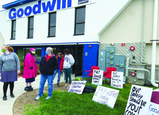 Goodwill employees outside Williston store with protest signs