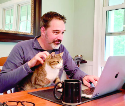 Matt Dodds of South Road Williston sits at his laptop with his cat