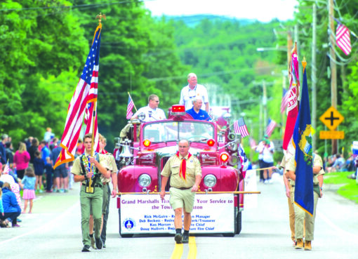 Scouts bearing flags lead the parade followed by the Grand Marshals in a vintage fire truck.