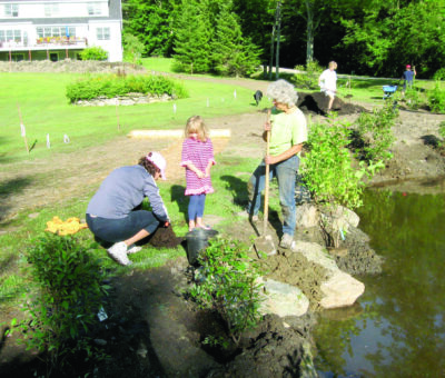 Two women and a child plant shrubs near the Lake Iroquois shoreline in 2021