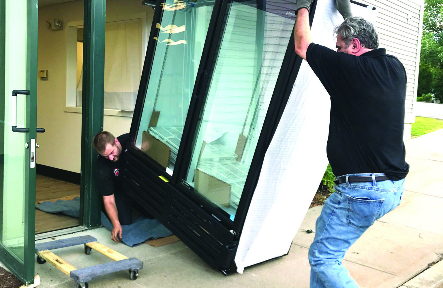 Tow men move a large commercial refrigerator into the Williston Community Food Shelf